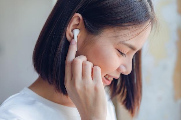 Kobiety słuchają muzyki z białych słuchawek. za pomocą rąk dotknij, aby użyć różnych funkcji.