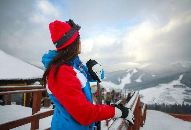 Kobiety snowboarder w zimie przy ośrodkiem narciarskim i niebem