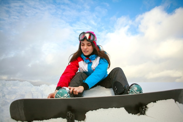 Kobiety snowboarder zasznurowywa przy wierzchołkiem góra na niebieskim niebie