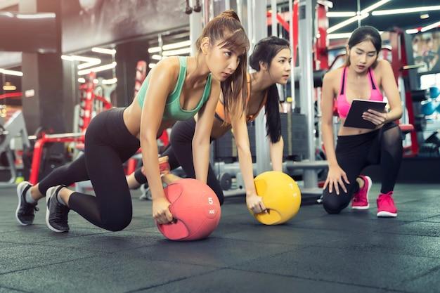 Kobiety sportowe ćwiczą razem w siłowni z trenerem