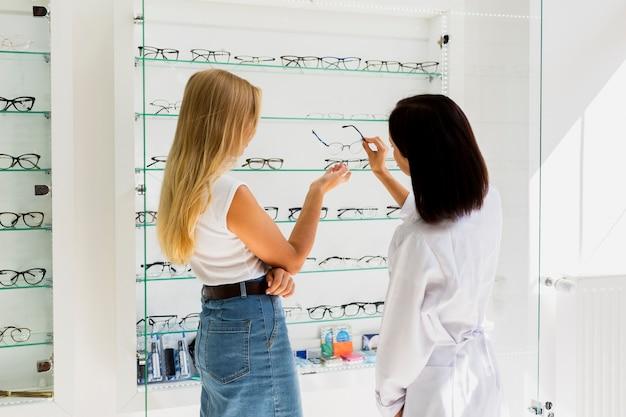 Kobiety sprawdzają eyeglasses ramę w sklepie