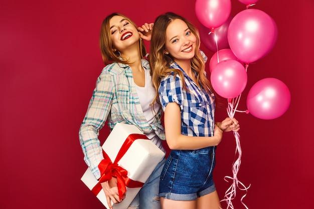 Kobiety stanowią duże pudełko i różowe balony