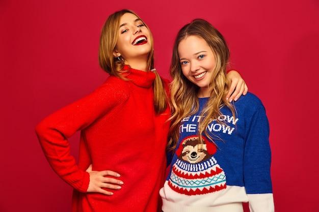 Kobiety stojące w stylowych zimowych ciepłych swetrach na czerwonej ścianie