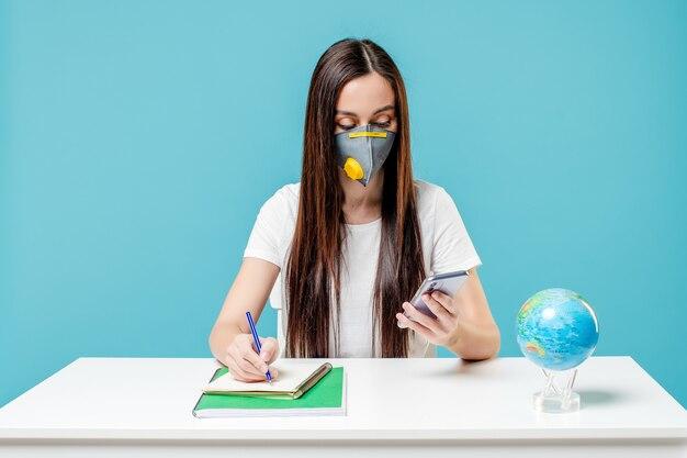 Kobiety studiowanie z planety ziemi kulą ziemską i telefon z książkami jest ubranym maskę
