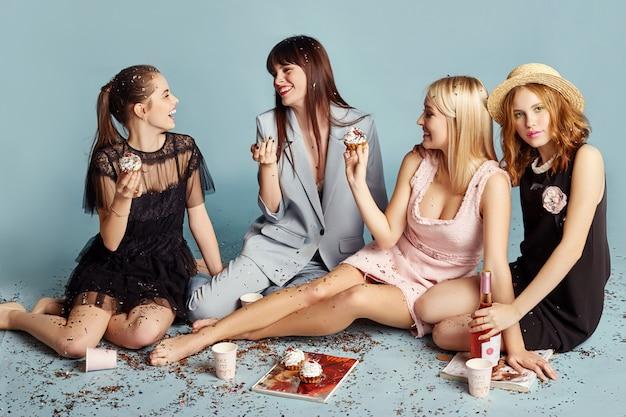 Kobiety świętują przyjęcie świąteczne, śmiejąc się i jedząc ciasta pod latającymi konfetti.