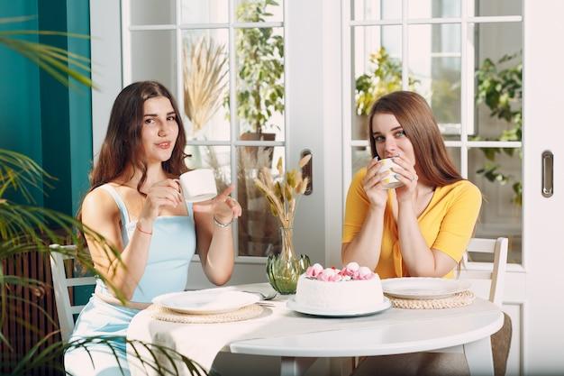 Kobiety szczęśliwych przyjaciół w domu siedząc i uśmiechając się z białym tortem urodzinowym i filiżanką herbaty.