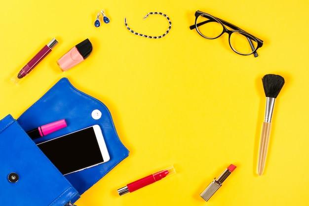 Kobiety torebka, produkty kosmetyczne, smartphone, okulary na jasnym żółtym tle, widok z góry