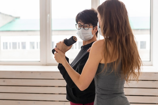 Kobiety trenujące razem po leczeniu koronawirusa z użyciem maseczek na twarz