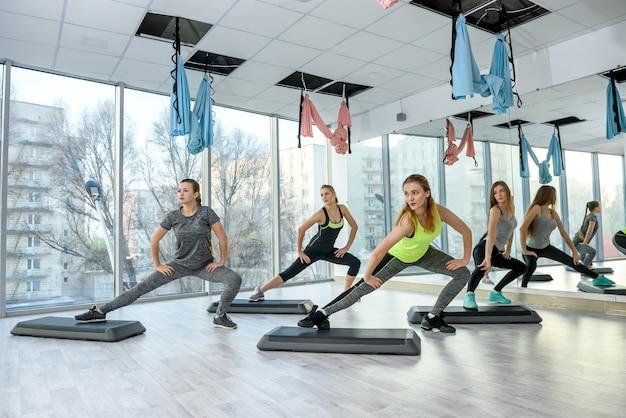 Kobiety trenujące w siłowni wykonywanie ćwiczeń rozciągających
