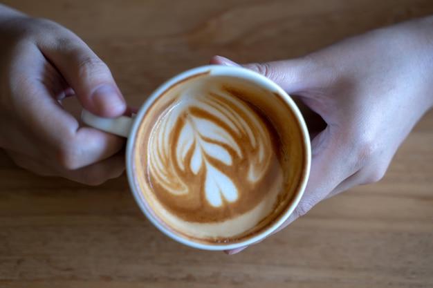 Kobiety trzyma filiżankę, drewniana stołowa kawiarnia podczas gdy mieć kawę