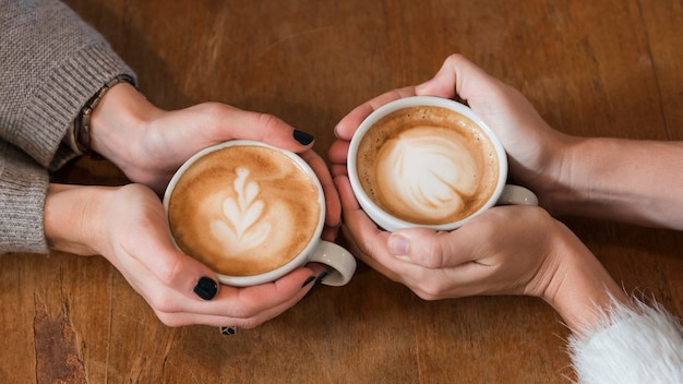 Kobiety trzyma filiżanki kawy na stole