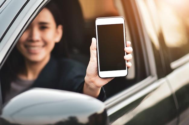Kobiety trzyma mądrze telefon pokazuje telefonu komórkowego parawanowego obsiadanie w samochodzie