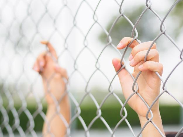 Kobiety trzyma rękę trzyma ogrodzenie na plenerowej scenerii podczas światła dziennego.