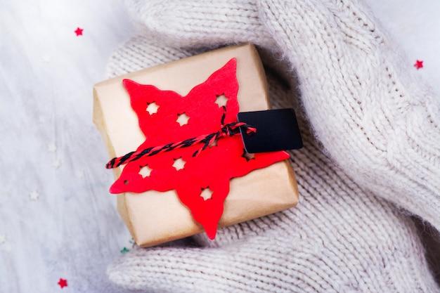 Kobiety trzymają małe pudełko prezentowe w rękach noszone w białych rękawiczkach