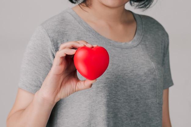 Kobiety trzymające czerwone serce i pokazujące.
