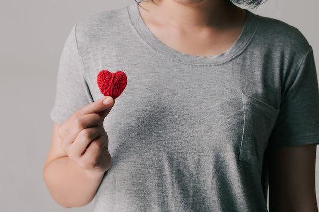 Kobiety trzymające i pokazujące czerwone serce. międzynarodowy lub krajowy dzień kardiologii.