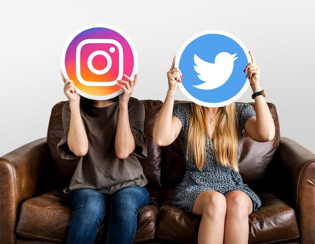 Kobiety trzymające ikony mediów społecznościowych