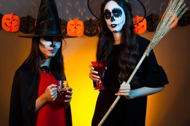 Kobiety trzymające napoje przebrany za czarownice
