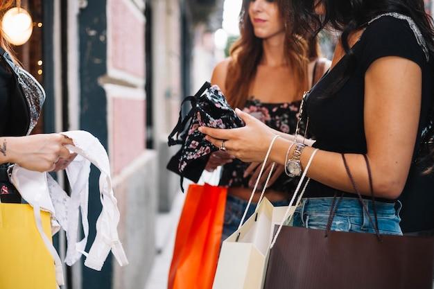Kobiety trzymające papierowe torby i bieliznę