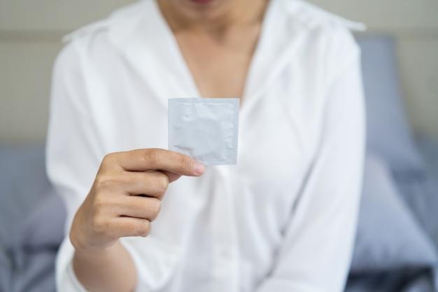 Kobiety trzymające prezerwatywę siedzą na łóżku w sypialni