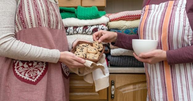 Kobiety trzymające w kuchni filiżankę kawy i ciastek ubrane w świąteczne fartuchy z wieloma różnymi swetrami.