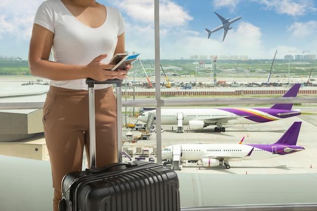 Kobiety turystyczna pozycja z bagażem przy lotniskowym okno podczas gdy czekający przy abordaż bramą przed odjazdem przy holem.
