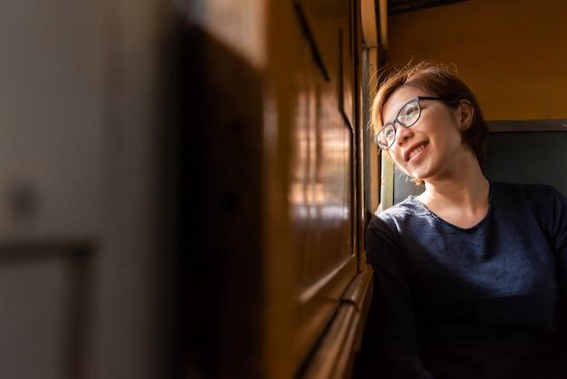 Kobiety turystyczny patrzeć na zewnątrz okno pociągu.