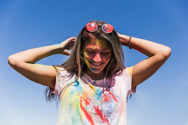 Kobiety twarz z holi kolorami stoi przeciw niebieskiemu niebu