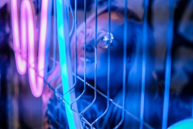 Kobiety twarz z szkłami w metal ramie odbija neonowego światło, selec