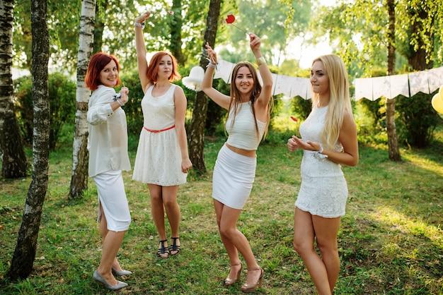 Kobiety ubrane w białe sukienki bawiące się na panieńskim przyjęciu.