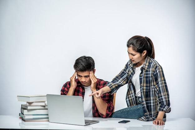 Kobiety uczą mężczyzn pracy z laptopami w pracy.