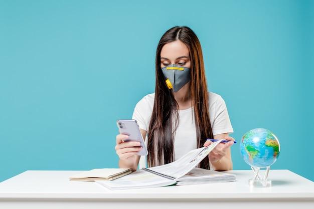 Kobiety uczenie się z planety ziemi kulą ziemską i telefon z książkami jest ubranym maskę