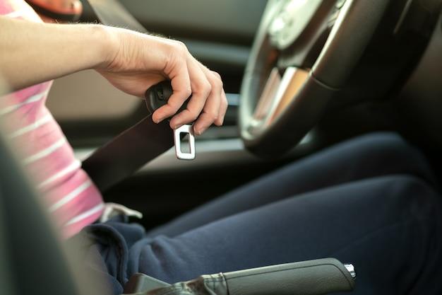Kobiety uczepienia pas bezpieczeństwa podczas gdy siedzący wśrodku samochodu