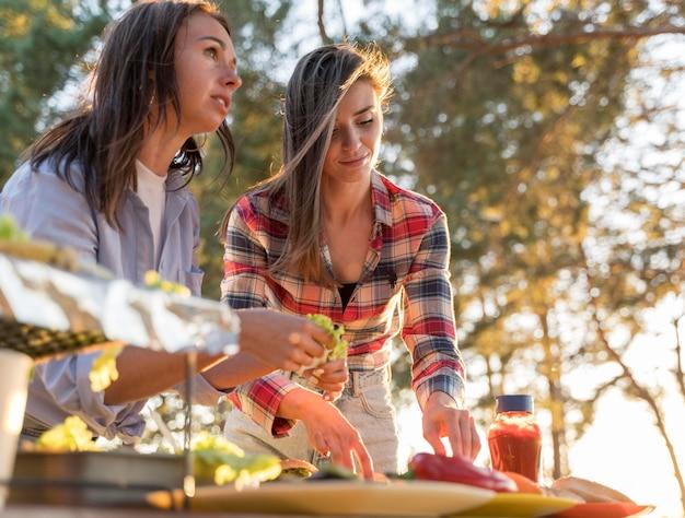 Kobiety układają na stole pyszne jedzenie dla przyjaciół