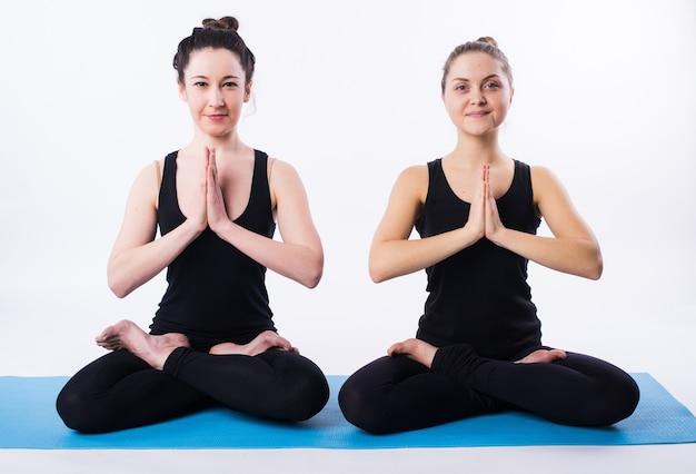 Kobiety uprawiają jogę i medytują w pozycji lotosu