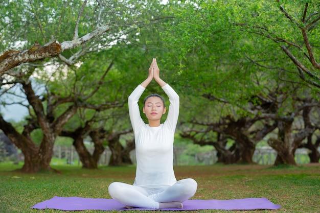 Kobiety uprawiają jogę w parku