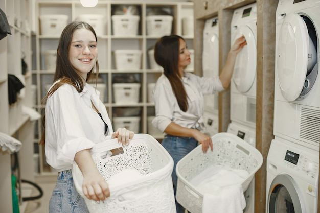 Kobiety używające pralki do prania. młode dziewczyny gotowe do prania ubrań. wnętrze, koncepcja procesu mycia