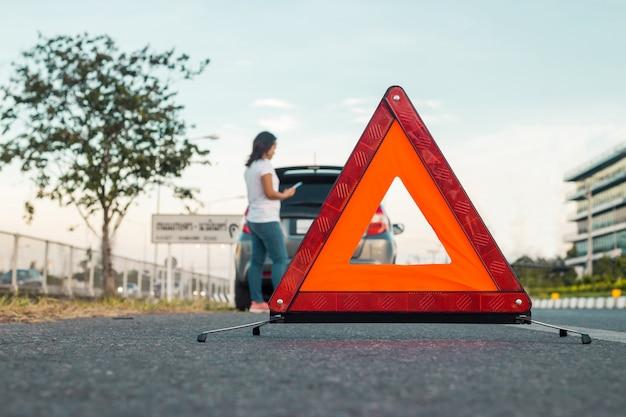 Kobiety używające telefonu komórkowego do robienia zdjęć swojego samochodu, który otwiera kaptur.