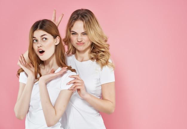 Kobiety w białych koszulkach stoją obok emocji przyjaźń na różowym tle