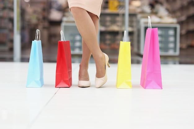 Kobiety w butach stoją obok kolorowych papierowych toreb na zakupy w centrum handlowym
