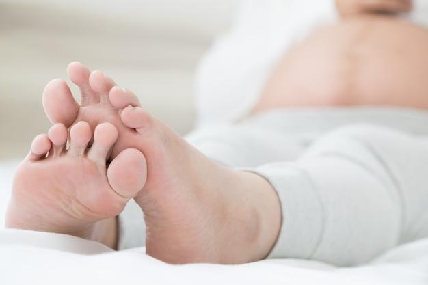 Kobiety w ciąży z azji południowo-wschodniej z obrzękami stóp, bólem stóp i leżeniem na łóżku w pokoju.