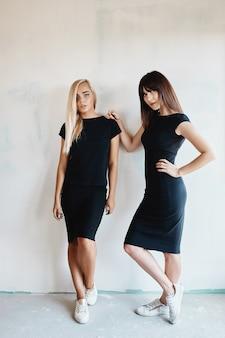 Kobiety w czarnej sukience pozowanie na ścianie