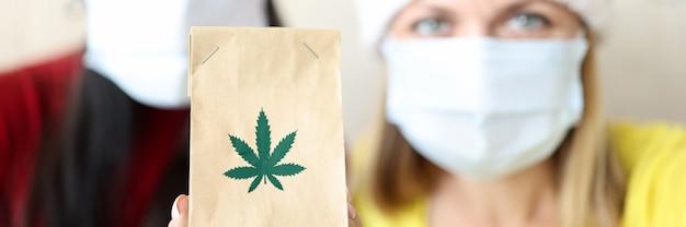 Kobiety w czerwonych czapkach świętego mikołaja i ochronnych maskach medycznych trzymające papierową torbę z ekstraktem z marihuany ...