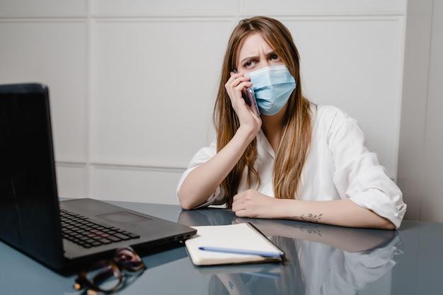 Kobiety w domu biuro z laptopem jest ubranym maskę i robi rozmowie telefonicza