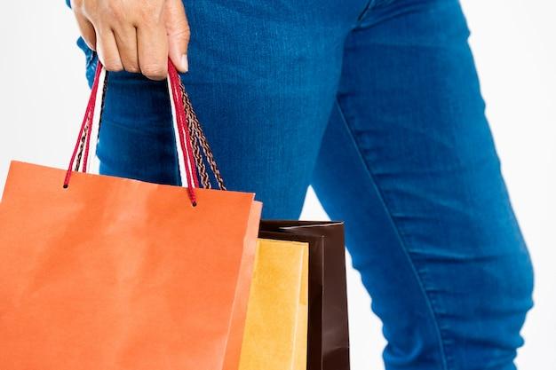 Kobiety w dżinsach, stojące i trzymające kolorowe torby na zakupy po zakupach