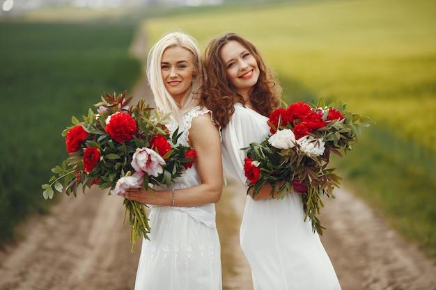 Kobiety w eleganckiej sukni stojącej w polu letnim