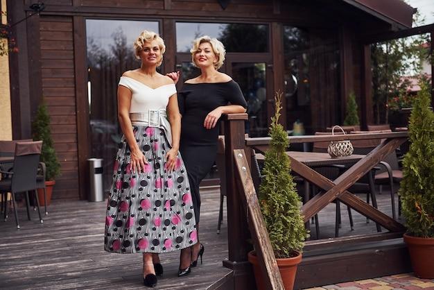 Kobiety w formalnych ubraniach stoją razem w pobliżu budynku w ciągu dnia.