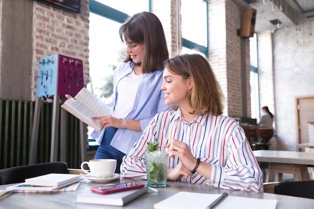 Kobiety w kawiarni omawiając książkę