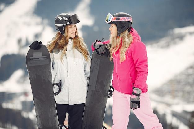 Kobiety w kombinezonach snowboardowych. sportsmenki na górze ze snowboardem w rękach na horyzoncie. koncepcja sportu