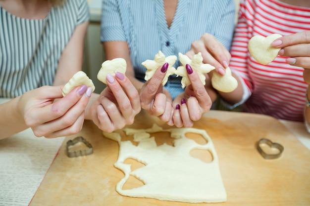 Kobiety w kuchni przygotowujące ciasteczka z ciasta